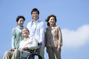 車椅子に座るシニア男性と笑顔の家族の写真素材 [FYI04779442]