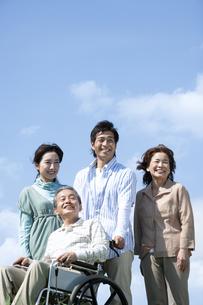 車椅子に座るシニア男性と笑顔の家族の写真素材 [FYI04779443]