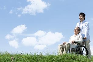 車椅子に座るシニア男性と笑顔の男性の写真素材 [FYI04779444]