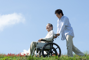 車椅子に座るシニア男性と笑顔の男性の写真素材 [FYI04779452]