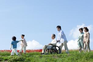 車椅子に座るシニア男性と笑顔の家族の写真素材 [FYI04779455]