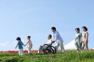 車椅子に座るシニア男性と笑顔の家族の写真素材 [FYI04779457]