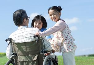 車椅子に座るシニア男性と孫の写真素材 [FYI04779458]