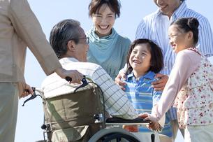 車椅子に座るシニア男性と笑顔の家族の写真素材 [FYI04779462]