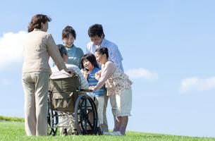 車椅子に座るシニア男性と笑顔の家族の写真素材 [FYI04779466]