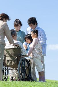 車椅子に座るシニア男性と笑顔の家族の写真素材 [FYI04779467]