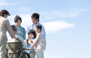 車椅子に座るシニア男性と笑顔の家族の写真素材 [FYI04779468]