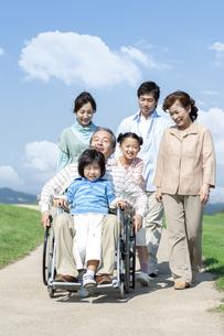 車椅子に座るシニア男性と笑顔の家族の写真素材 [FYI04779472]