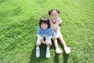 芝生に座る女の子と男の子の写真素材 [FYI04779495]