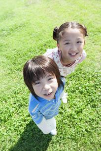 芝生に立つ女の子と男の子の写真素材 [FYI04779497]