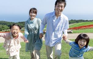 手を繋ぐ笑顔の家族の写真素材 [FYI04779500]