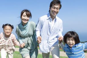 手を繋ぐ笑顔の家族の写真素材 [FYI04779504]