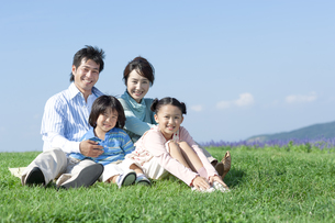 芝生に座る家族の写真素材 [FYI04779509]