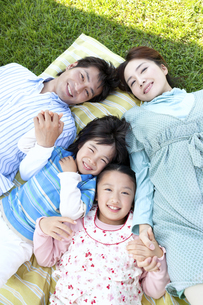 芝生に寝転ぶ家族の写真素材 [FYI04779515]