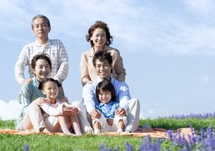 芝生に座る三世代家族の写真素材 [FYI04779517]