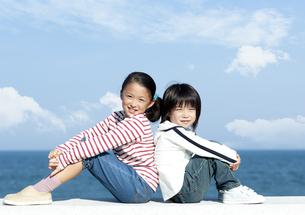 防波堤に座る女の子と男の子の写真素材 [FYI04779527]