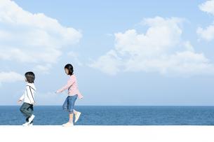 防波堤を歩く女の子と男の子の写真素材 [FYI04779529]