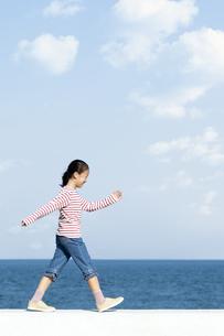 防波堤を歩く女の子の写真素材 [FYI04779531]