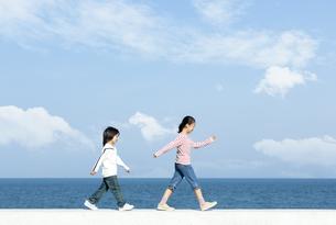 防波堤を歩く女の子と男の子の写真素材 [FYI04779532]