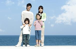 防波堤に立つ笑顔の家族の写真素材 [FYI04779536]