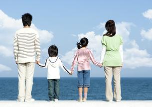 防波堤に立つ後姿の家族の写真素材 [FYI04779539]