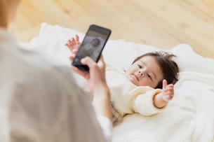 赤ちゃんの撮影をする母親の写真素材 [FYI04779673]