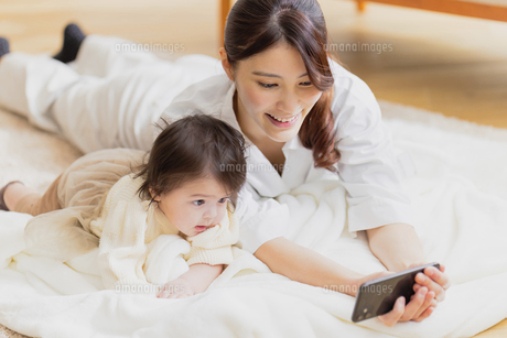 赤ちゃんの撮影をする母親の写真素材 [FYI04779674]