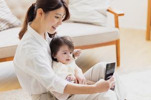 赤ちゃんの撮影をする母親の写真素材 [FYI04779675]