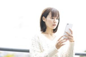 スマートフォンを見つめる女性の写真素材 [FYI04779855]