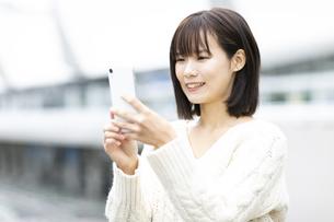 スマートフォンを見つめる笑顔の女性の写真素材 [FYI04779856]