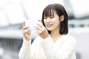 スマートフォンを見つめる笑顔の女性の写真素材 [FYI04779858]