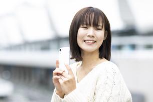 スマートフォンを持つ笑顔の女性の写真素材 [FYI04779862]