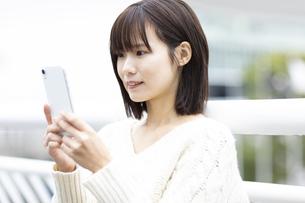 スマートフォンを見つめる女性の写真素材 [FYI04779870]