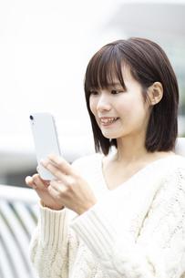 スマートフォンを操作する笑顔の女性の写真素材 [FYI04779871]