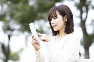 スマートフォンを操作する笑顔の女性の写真素材 [FYI04779878]