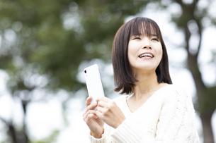スマートフォンを持つ笑顔の女性の写真素材 [FYI04779879]