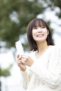 スマートフォンを持つ笑顔の女性の写真素材 [FYI04779882]