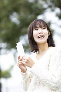 スマートフォンを持つ笑顔の女性の写真素材 [FYI04779883]