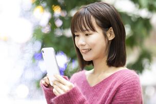 スマートフォンを操作する笑顔の女性の写真素材 [FYI04779894]