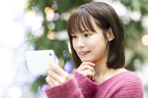 スマートフォンを見る笑顔の女性の写真素材 [FYI04779895]