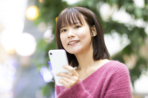 スマートフォンを持つ笑顔の女性の写真素材 [FYI04779898]