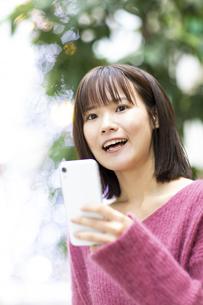 スマートフォンを持つ笑顔の女性の写真素材 [FYI04779899]