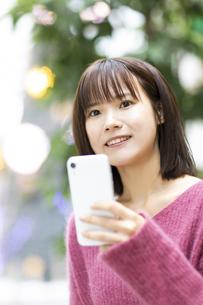 スマートフォンを持つ笑顔の女性の写真素材 [FYI04779900]