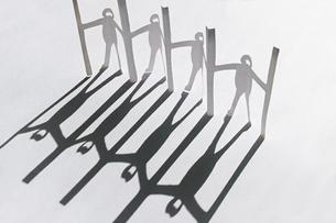 白い紙の上に斜めに置いた新型コロナ対策で衝立を挟んで繋がる人々の切り紙。斜めの黒く長い影。の写真素材 [FYI04779910]