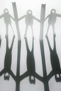白い紙の上に置いた新型コロナ対策で衝立を挟んで繋がる人々の切り紙と長く伸びた影。縦長。の写真素材 [FYI04779912]