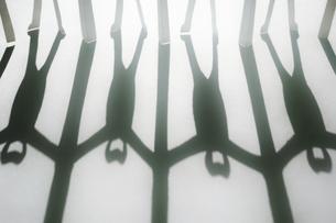 白い紙の上に伸びた新型コロナ対策で衝立を挟んで繋がる人々の切り紙の黒い影。の写真素材 [FYI04779914]