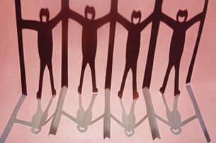 赤い紙の上に映る新型コロナ対策で衝立を挟んで繋がる人々の切り紙の黒い影。の写真素材 [FYI04779915]
