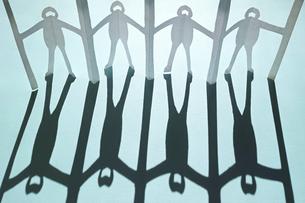 水色の紙の上に立てた新型コロナ対策で衝立を挟んで繋がる人々の切り紙。黒くて長い影。の写真素材 [FYI04779916]
