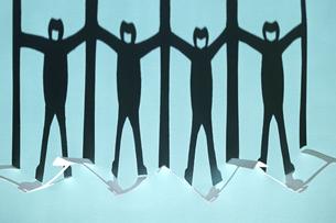 青い紙の上に映る新型コロナ対策で衝立を挟んで繋がる人々の切り紙の黒い影。強いコントラスト。の写真素材 [FYI04779917]