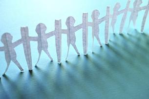 青い紙の上に立てた新型コロナ対策で衝立を挟んで繋がる人々の切り紙。右上がりの斜め。の写真素材 [FYI04779921]